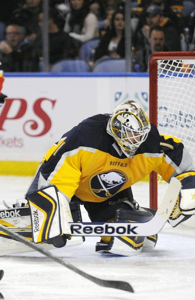 Buffalo Sabres goaltender Jhonas Enroth (1), of Sweden, reacts to the puck while Calgary Flames center Paul Byron (32), gives chase during the second period of an NHL hockey game in Buffalo, N.Y., Saturday Dec. 14, 2013. Calgary won 2-1