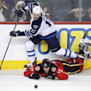Winnipeg Jets' Olli Jokinen, top, takes a tripping penalty on Calgary Flames' Kevin Westgarth during second period NHL action in Calgary, Alberta, Friday, April 11, 2014 The Associated Press