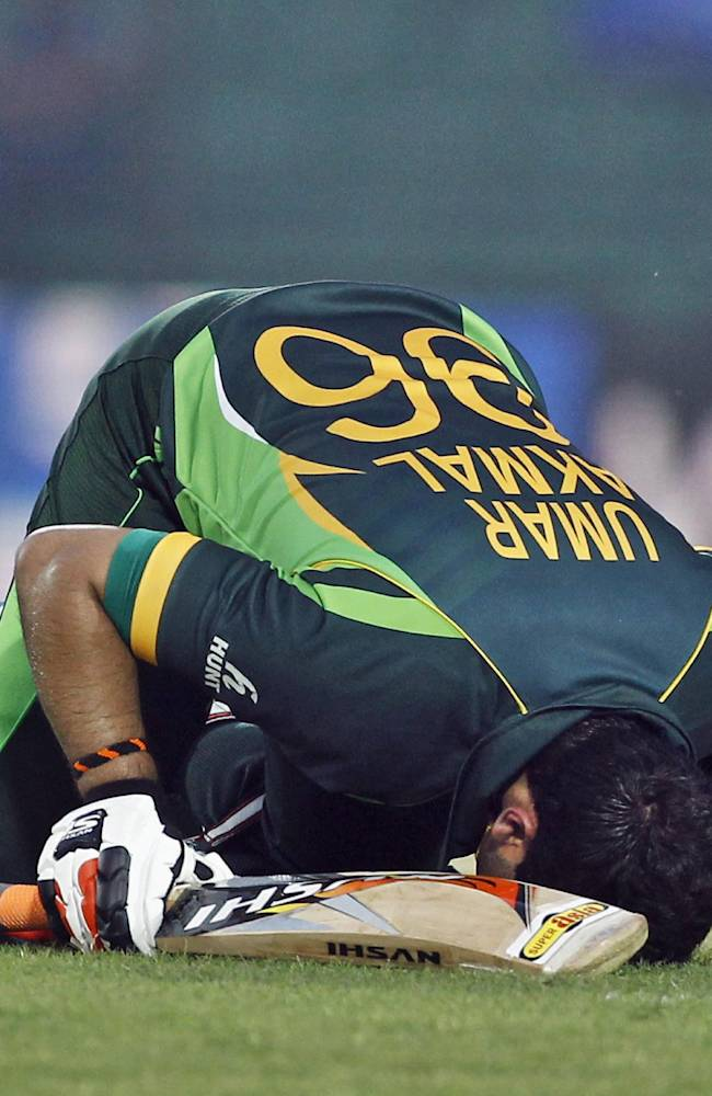 Pakistan's Umar Akmal kisses the ground after scoring a century during the Asia Cup one-day international cricket tournament against Afghanistan in Fatullah, near Dhaka, Bangladesh, Thursday, Feb. 27, 2014