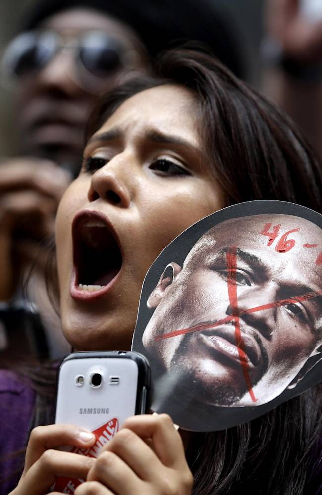 A Marcos Maidana fan holding a picture of Floyd Mayweather yells during an outdoor news conference in Times Square, New York, Monday, July 14, 2014. Mayweather will fight Maidana for the second time in Las Vegas, Nevada on Sept. 13, 2014