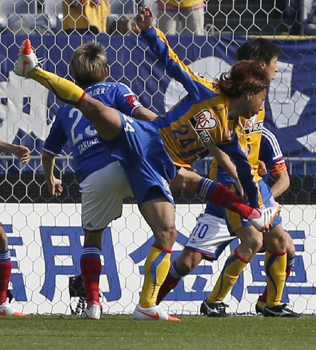 Vegalta Sendai's Shingo Akamine (24) scores a goal against Yokohama F. Marinos' Sho Ito during a J-League soccer match in Yokohama, near Tokyo, Saturday, April 12, 2014