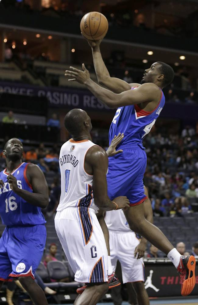 Philadelphia 76ers' Gani Lawal, top right, drives past Charlotte Bobcats' Bismack Biyombo (0) as 76ers' Mac Koshwal (16) looks on during the second half of a preseason NBA basketball game in Charlotte, N.C., Thursday, Oct. 17, 2013. The Bobcats won 110-84