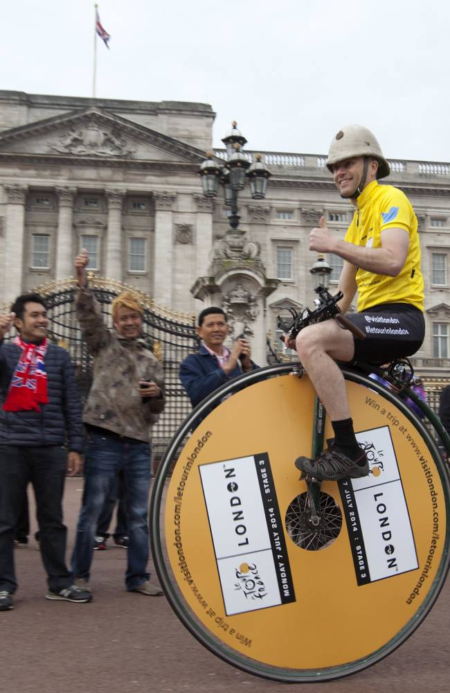 IMAGE DISTRIBUTED FOR VISIT LONDON - Joff Summerfield, from Greenwich in south east London, rides his penny farthing past Buckingham Palace in central London on Wednesday, April 2, 2014. Joff is training ahead of this year's Spring Classics to celebrate the Tour de France coming to London on the 7th of July. Joff, who circumnavigated the world on a penny farthing in 2006, will take part in his first challenge on the 5th of April in the Tour of Flanders. (David Parry/Visit London via AP Images)