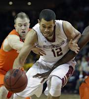 Boston College forward Ryan Anderson (12) attempts to drive through the defense of Syracuse forward Rakeem Christmas, right, and Syracuse guard Trevor Cooney (10) during the first half of their NCAA college basketball game at Boston College in Boston, Monday, Jan. 13, 2014. (AP Photo/Stephan Savoia)