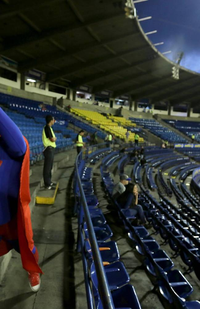 In this Nov. 27, 2013, Tiburones Jose Perez, dressed in a Superman costume, jokes with rival fans prior a baseball game between Tiburones of La Guira and Leones of Caracas at Estadio Universitario in Caracas, Venezuela.  It's about two months before pitchers and catchers report to spring training in the U.S., but in Venezuela the nation's fiercely competitive professional league is in full swing, and it's drawn the biggest contingent of American players in decades