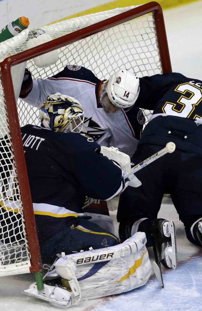 Columbus Blue Jackets' Blake Comeau, center, slides into the net along with St. Louis Blues goalie Brian Elliott, left, and Blues' Jordan Leopold during the third period of an NHL hockey game Saturday, Jan. 4, 2014, in St. Louis. The Blues won 6-2