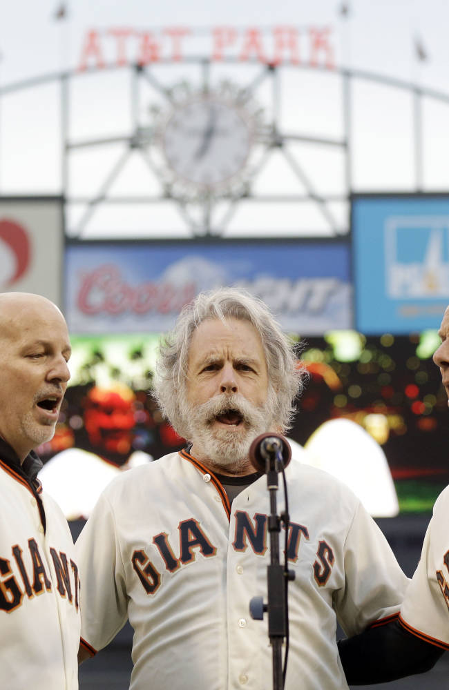 File - In this Aug. 5, 2013 file photo, San Francisco Giants third base coach Tim Flannery, right, and his brother Tom, left, sing the national anthem with Bob Weir of the Grateful Dead before a baseball game against the Milwaukee Brewers in San Francisco. Flannery, the San Francisco Giants' third-base coach and musician, presented the family of Bryan Stow with $96,000 during the weekend to help with his care as he continues to deal with traumatic injuries and brain damage from being severely beaten outside Dodger Stadium on opening day 2011