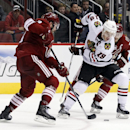 Chicago Blackhawks center Jonathan Toews (19) and Phoenix Coyotes defenseman Keith Yandle battle for the puck in the third period of an NHL hockey game on Saturday, Nov. 30, 2013, in Glendale, Ariz The Associated Press