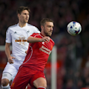 Liverpool's Rickie Lambert, foreground, fights for the ball against Swansea's Federico Fernandez, during the English League Cup soccer match between Liverpool and Swansea at Anfield Stadium, Liverpool, England, Tuesday Oct. 28, 2014