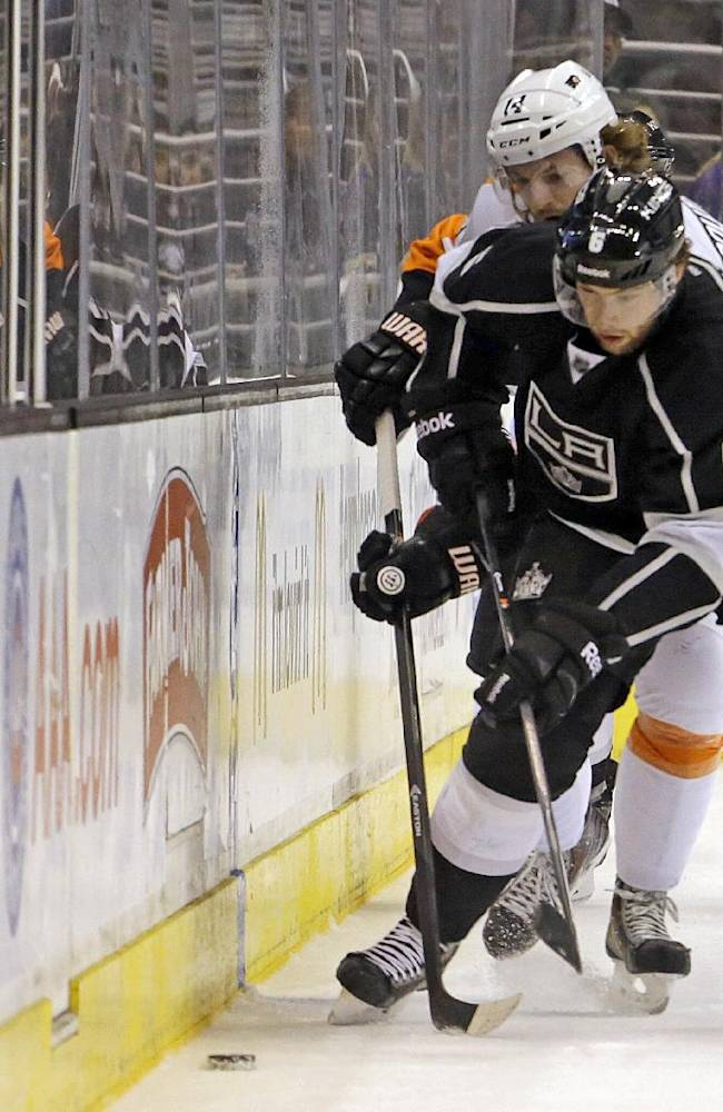 Los Angeles Kings defenseman Jake Muzzin (6) and Philadelphia Flyers center Sean Couturier (14) tangle in the third period of an NHL hockey game in Los Angeles Saturday, Feb. 1, 2014.  The Flyers won, 2-0