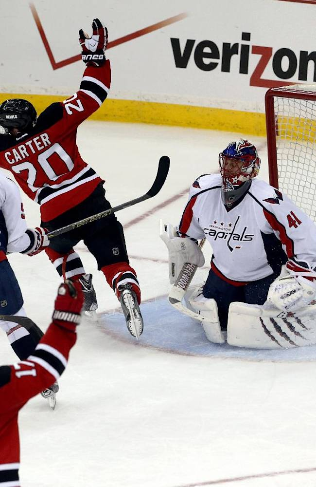 New Jersey Devils' Ryan Carter (20) and Michael Ryder (17) celebrate a goal by Carter as Washington Capitals' Jay Beagle (83), Mike Green (52) and Jaroslav Halak (41), of Slovakia, react during the third period of an NHL hockey game, Friday, April 4, 2014, in Newark, N.J. The Devils won 2-1