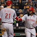 Cincinnati Reds' Todd Frazier (21) is greeted by Johnny Cueto (47) after scoring on a double by Reds' Zack Cozart off Pittsburgh Pirates starting pitcher Edinson Volquez during the seventh inning of a baseball game in Pittsburgh Tuesday, April 22, 2014 Th