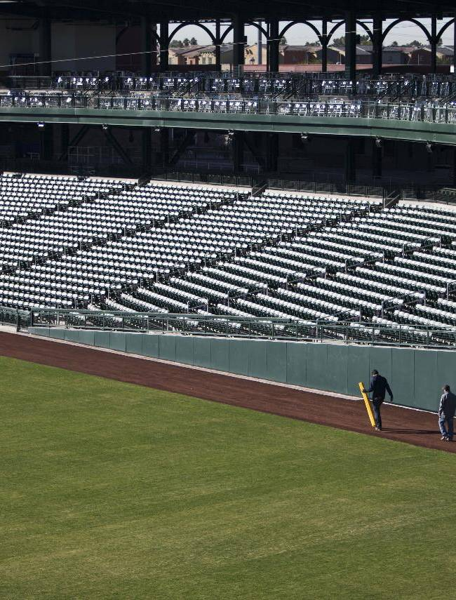 People walk past stands during a tour of the new baseball spring training stadium for the Chicago Cubs, Wednesday, Jan. 15, 2014, in Mesa, Ariz. The first Cactus League game at the stadium is scheduled for Feb. 27
