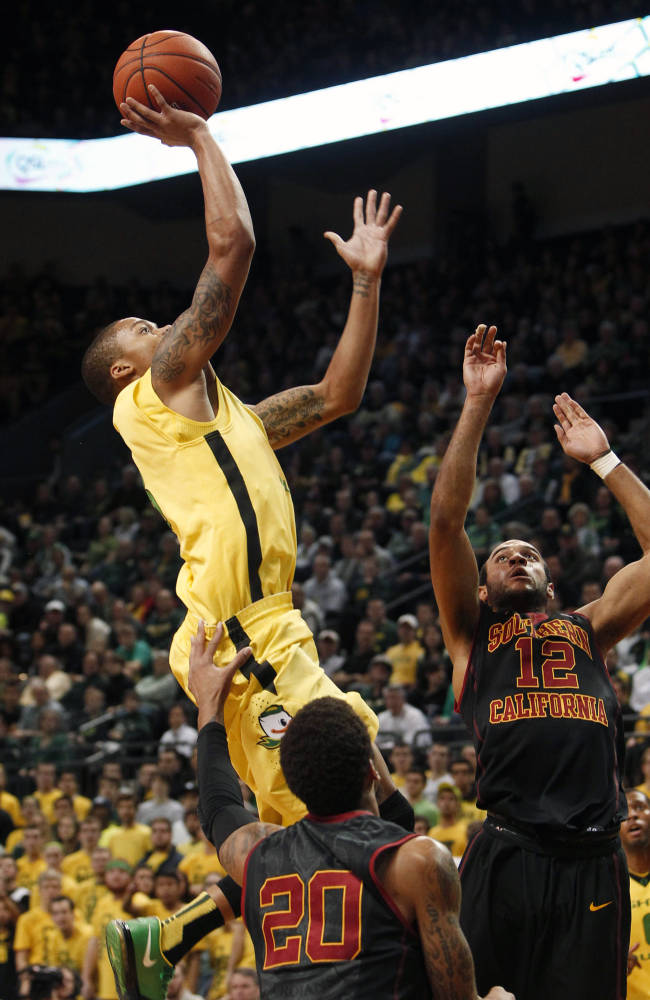 Oregon's Joseph Young, left, goes up for two of his game high 21 points against Southern California's J.T. Terrell and Julian Jacobs during the first half of an NCAA college basketball game in Eugene, Ore. on Saturday, Feb. 1, 2014