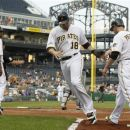 Pittsburgh Pirates' Neil Walker (18) is greeted at home plate by teammate Alex Presley (7) after scoring with Presley and James McDonald (53) on a bases-loaded double by Andrew McCutchen in the second inning of a baseball game against the Minnesota Twins, Thursday, June 21, 2012, in Pittsburgh. (AP Photo/Keith Srakocic)