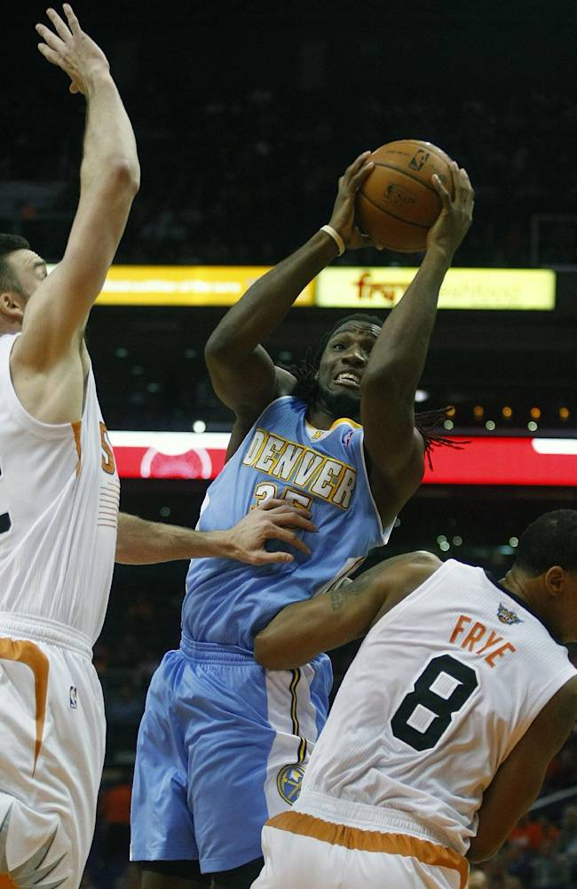 Denver Nuggets power forward Kenneth Faried (35) shoots between Phoenix Suns center Miles Plumlee (22) and Channing Frye (8) in the first quarter during an NBA basketball game on Friday, Nov. 8, 2013, in Phoenix