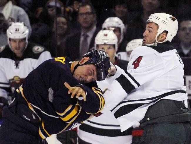 Buffalo Sabres center Cody McCormick (8) grimaces after a punch by Minnesota Wild defenseman Clayton Stoner (4) during a fight in the first period of an NHL hockey game in Buffalo, N.Y., Monday, Oct. 14, 2013. Minnesota won 2-1