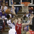 Sacramento Kings guard Ben McLemore, left, goes the basket against Houston Rockets Omer Asik, of Turkey, center, during the fourth quarter of an NBA basketball game in Sacramento, Calif., Tuesday Feb. 25, 2014. The Rockets won 129-103 The Associated Pre
