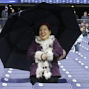 A fan stands under an umbrella on Saturday, April 19, 2014, during Washington's spring NCAA college football game in Seattle The Associated Press