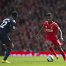 Liverpool's Raheem Sterling, right, takes the ball downfield past Southampton's Victor Wanyama during their English Premier League soccer match at Anfield Stadium, Liverpool, England, Sunday Aug. 17, 2014. Liverpool won the match 2-1