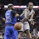 San Antonio Spurs' Kawhi Leonard (2) passes the ball around Dallas Mavericks' Vince Carter (25) during the first half of an NBA basketball game, Sunday, March 2, 2014, in San Antonio The Associated Press