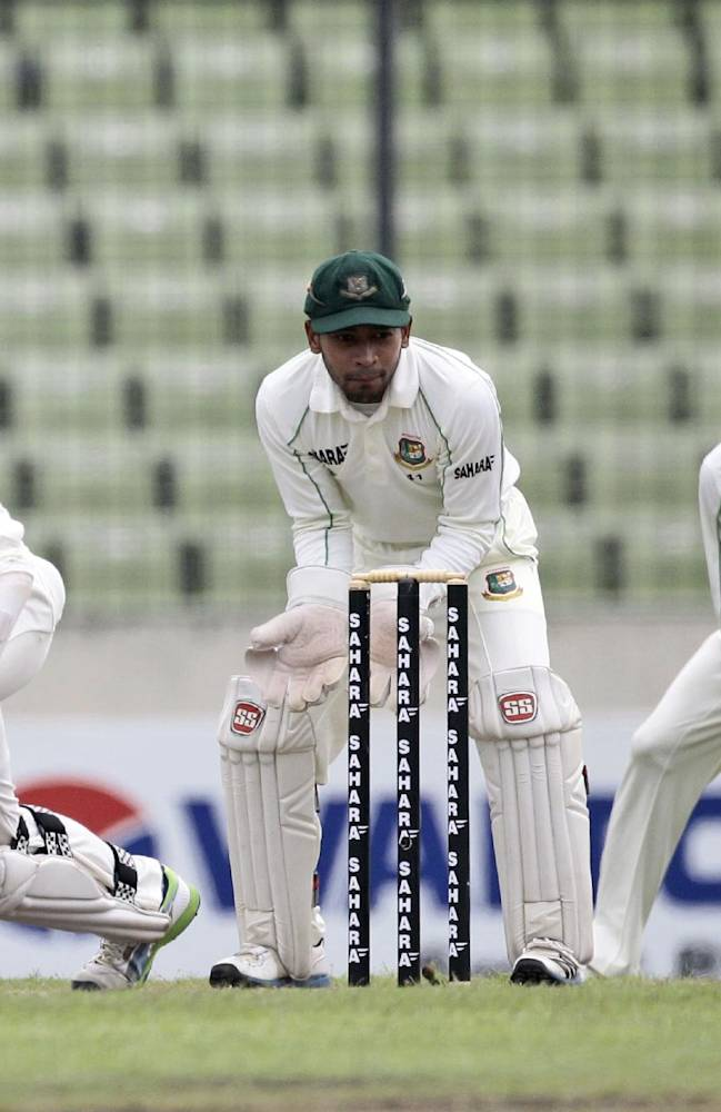 New Zealand's Kane Williamson bats, as Bangladesh's captain Mushfiqur Rahim, second left, looks at the ball on the third day of the second cricket test match in Dhaka, Bangladesh, Wednesday, Oct. 23, 2013