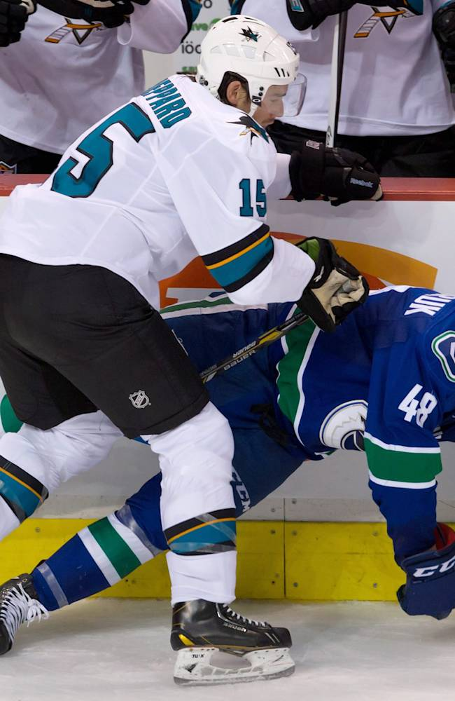 San Jose Sharks' James Sheppard, left, checks Vancouver Canucks' Hunter Shinkaruk during second period pre-season NHL hockey action in Vancouver, British Columbia on Monday Sept. 16, 2013