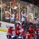 Fans celebrate behind the glass as the Chicago Blackhawks celebrate Bryan Bickell's game winner in overtime in Game 1 of an N