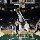 Milwaukee Bucks' Giannis Antetokounmpo, front, dunks during the first half of an NBA basketball game against the San Antonio Spurs Wednesday, Dec. 11, 2013, in Milwaukee. (AP Photo/Morry Gash)