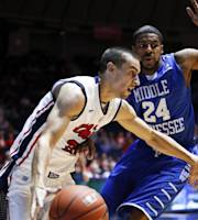 Mississippi guard Marshall Henderson, left, drives up court as Middle Tennessee State's Kerry Hammonds II (24) defends in the first half of an NCAA college basketball game in Oxford, Miss., Saturday, Dec. 14, 2013. (AP Photo/Rogelio V. Solis)