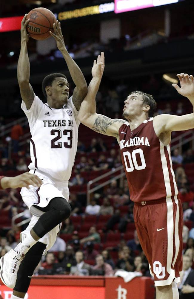 Texas A&M's Jamal Jones (23) goes up against Oklahoma's Frank Booker (00) during the first half of an NCAA college basketball game Saturday, Dec. 21, 2013, in Houston