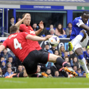 Everton's Romelu Lukaku right, has his shot handled by Manchester United's Phil Jones left, which awards Everton a penalty during their English Premier League soccer match at Goodison Park in Liverpool, England, Sunday April 20, 2014