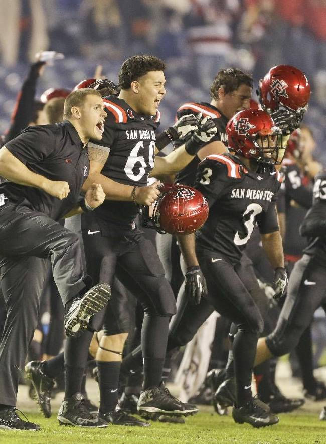 The San Diego State races on the field celebrating their 34-31 overtime victory against Boise State in an NCAA college football game Saturday, Nov. 23, 2013, in San Diego