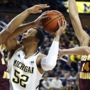Michigan forward Jordan Morgan (52) is defended by Central Michigan guard Derrick Richardson Jr., left, and forward Blake Hibbitts (24) while attempting a shot in the first half of an NCAA college basketball game, Saturday, Dec. 29, 2012, in Ann Arbor, Mich. (AP Photo/Duane Burleson)
