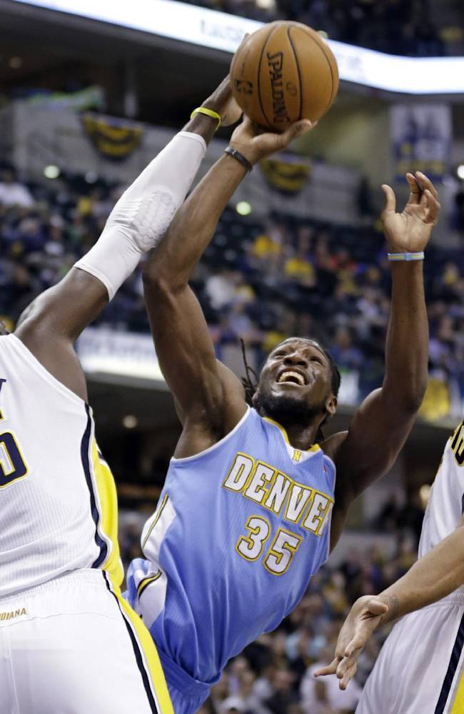 Denver Nuggets forward Kenneth Faried (35) shoots between Indiana Pacers center Roy Hibbert (55) and David West in the first half of an NBA basketball game in Indianapolis, Monday, Feb. 10, 2014