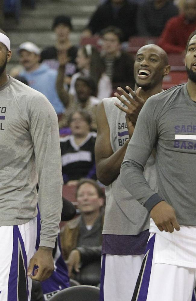 Sacramento Kings' DeMarcus Cousins, left, Travis Outlaw, center and Derrick Williams celebrate during the closing moments of the Kings' 112-97 win over the Dallas Mavericks in an NBA basketball game in Sacramento, Calif., Monday, Dec. 9, 2013