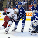 Columbus Blue Jackets' Artem Anisimov, left, and Toronto Maple Leafs' Jake Gardiner, center, scramble for a loose puck as Leafs' goalie James Reimer, right, is near during the third period of an NHL hockey game in Toronto on Monday, March 3, 2014 The Asso