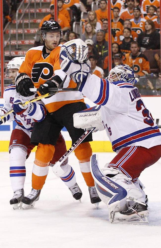 Philadelphia Flyers' Sean Couturier, center, reacts to the glove-save by New York Rangers' Henrik Lundqvist, right, of Sweden, while pushing away Rangers' Martin St. Louis during the third period in Game 4 of an NHL hockey first-round playoff series on Friday, April 25, 2014, in Philadelphia. The Flyers won 2-1