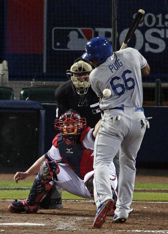 Los Angeles Dodgers' Yasiel Puig (66) is hit by a pitch thrown by Atlanta Braves starting pitcher Kris Medlen in the fourth inning of Game 1 of the National League Divisional Series, Thursday, Oct. 3, 2013, in Atlanta. Braves catcher Brian McCann, lower left, watches the play