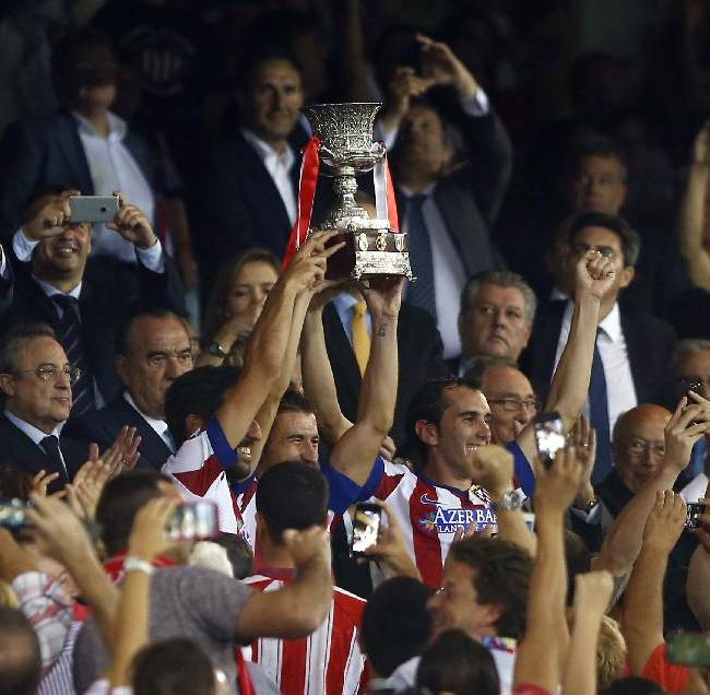 Atletico' players celebrates their victory with the trophy during a Spanish Supercup second leg soccer match between Real Madrid and Atletico Madrid at Vicente Calderon stadium in Madrid, Spain, early Saturday, Aug. 23, 2014