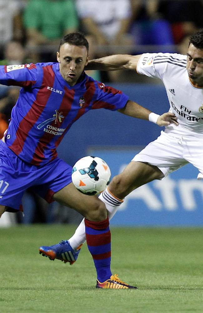 Real Madrid's Alvaro Arbeloa, right, battles for the ball with Levante's Javi Xumetra, left, during their La Liga soccer match at the Ciutat de Valecia stadium in Valencia, Spain, Saturday, Oct. 5, 2013