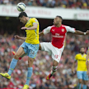 Arsenal's Alex Oxlade-Chamberlain, in the air with Crystal Palace's Mile Jedinak, during their English Premier League soccer match, at Emirates Stadium, in London, Saturday, Aug. 16, 2014