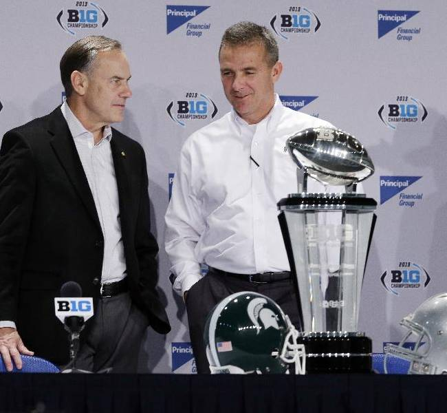 Michigan State head coach Mark Dantonio, left, talks with Ohio State head coach Urban Meyer during a news conference for the Big Ten Conference championship NCAA college football game Friday, Dec. 6, 2013, in Indianapolis. Ohio State will play Michigan State, Saturday for the championship