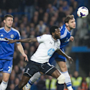 Chelsea's Branislav Ivanovic, right, vies for the ball with Tottenham Hotspur's Emmanuel Adebayor, center, during their English Premier League soccer match, at the Stamford Bridge Stadium in London, Sunday, March 8, 2014