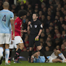 Manchester United's Marouane Fellaini, center left, reacts after receiving a yellow card from referee Michael Oliver for a challenge on Manchester City's Pablo Zabaleta, bottom, during their English Premier League soccer match at Old Trafford Stadium, Man