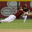 Arizona Diamondbacks' Aaron Hill dives for a ball hit by San Francisco Giants' Hunter Pence but is unable to hang on to the ball during the sixth inning of a baseball game, Wednesday, April 2, 2014, in Phoenix. Pence reached first base on a fielder's cho