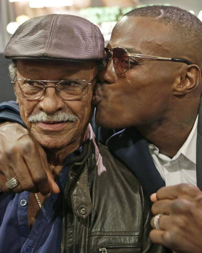Boxer Peter Quillan plants a kiss on his father Pedro's cheek before a news conference Wednesday, Oct. 23, 2013, in New York. Quillan is scheduled to defend his WBO middleweight title against Gabriel Rosado on Saturday in Atlantic City, N.J. The senior Quillan, born in Cuba, arrived in the United States during the 1980 Mariel boat lift