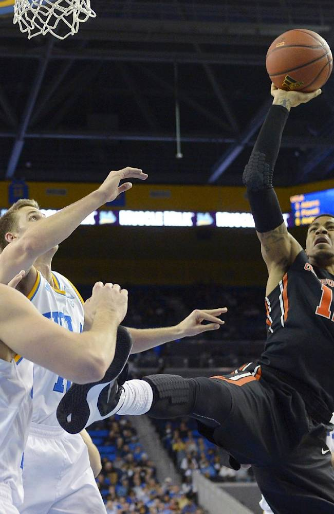 Oregon State forward Eric Moreland, right, puts up a shot as UCLA forward Travis Wear, left, and forward David Wear defend during the second half of an NCAA college basketball game, Sunday, March 2, 2014, in Los Angeles. UCLA won 74-69