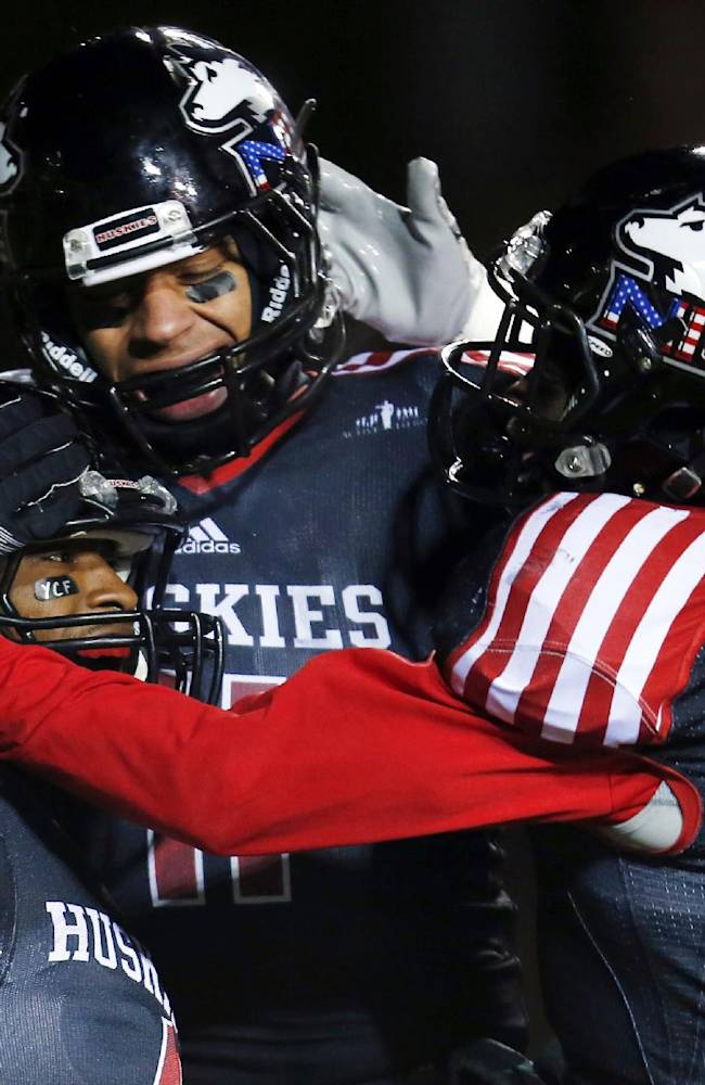 In this Wednesday, Nov. 13, 2013, file photo, Northern Illinois wide receiver Da'Ron Brown (4) celebrates with teammates Juwan Brescacin (11) and Tommylee Lewis (10) after a touchdown reception against Ball State during the first half of an NCAA college football game in DeKalb, Ill. College football is well into the patriotic era first evoked by the camouflage uniforms that debuted in the Army-Navy game five years ago