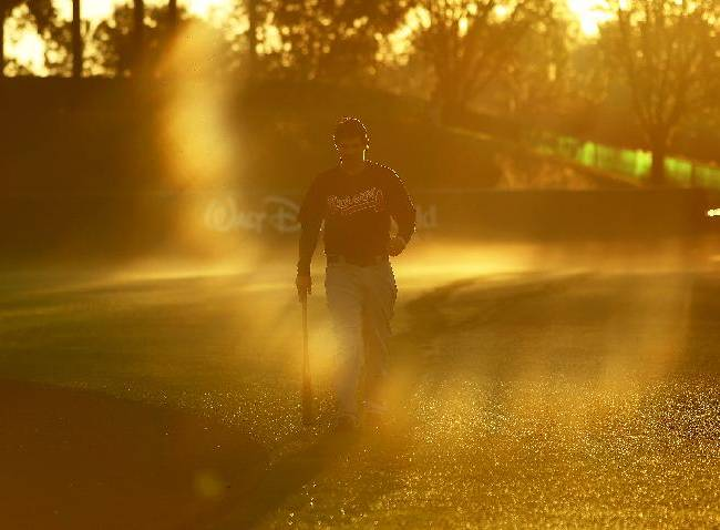 Atlanta Braves catcher Braeden Schlehuber walks across the field early Thursday morning, Feb. 20, 2014, before a baseball spring training workout in Kissimmee, Fla